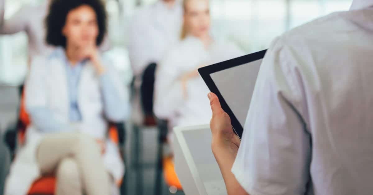 Medical professional leading care teams with a tablet