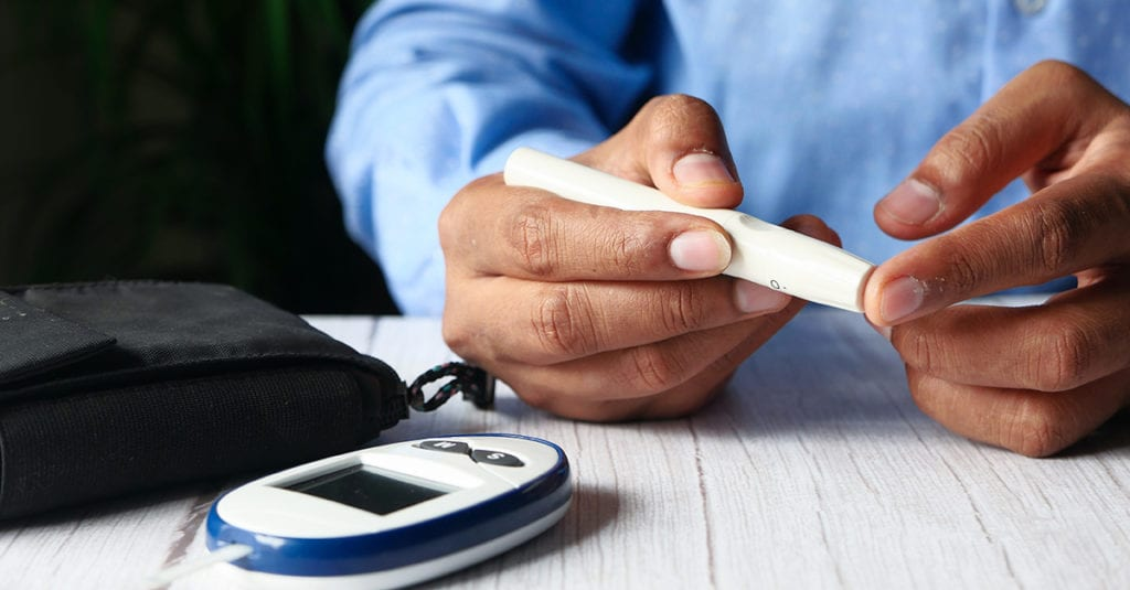 Person with diabetes measuring blood sugar level